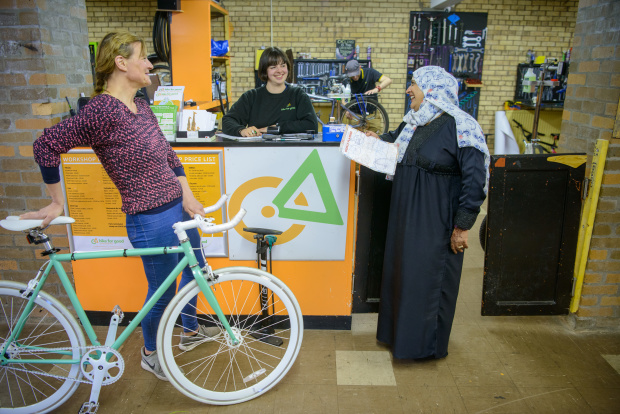 Two women stand, talking at a counter in Bike for Good's shop. A third woman stands behind the counter smiling. The women to the left of the image is holding a green and white bike.