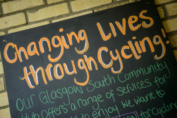 "A section of text is written on a blackboard: ""Changing lives through cycling! Our Glasgow South Community Hib offers a range of services for..."""