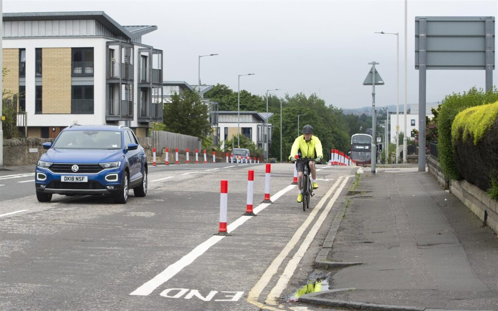 A person cycles uphill, seperated from motor traffic by orange and white stripped cylinders. A blue car is to one side of the cyclist, keeping a safe distance.
