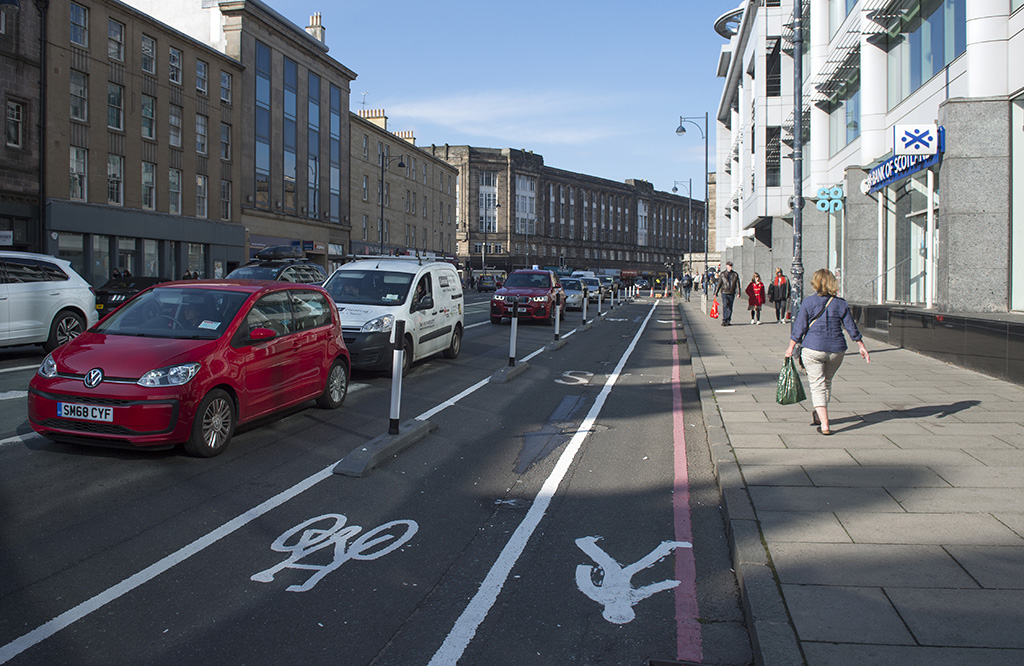 Black and white stripped cylinders mounted in kerb-like bases separate motor traffic and a cycle lane on Lothian Road