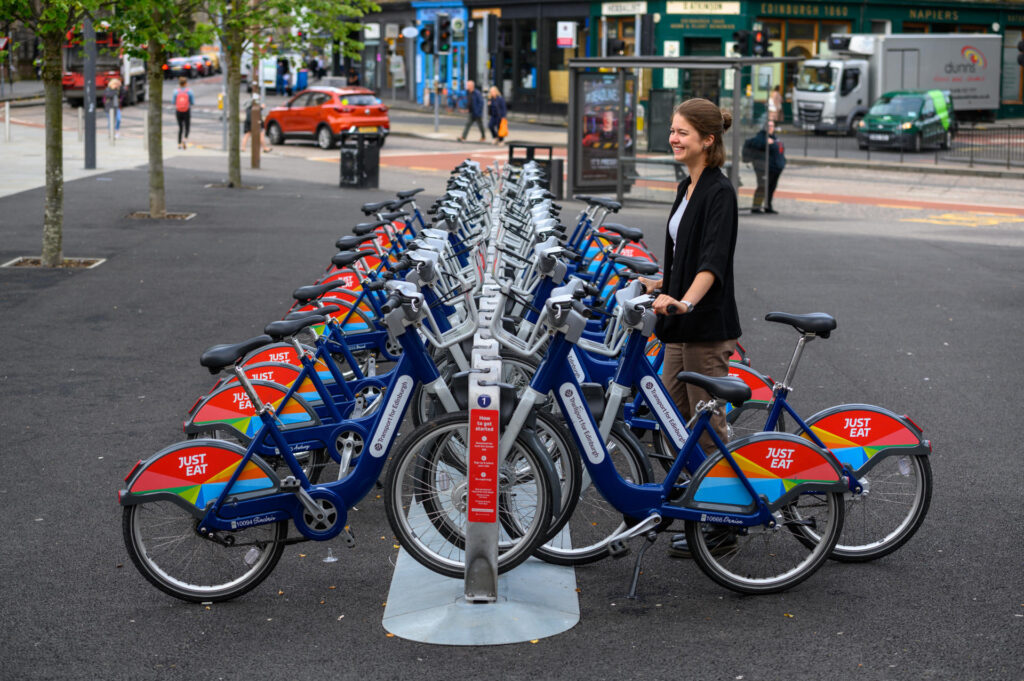 A person unlocks a Transport for Edinburgh hire bike from a rack on Bristo Square.